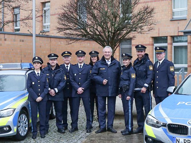 Innenminister Joachim Herrmann mit Polizistinnen und Polizisten in blauer Uniform. Foto: Bayerns Polizei