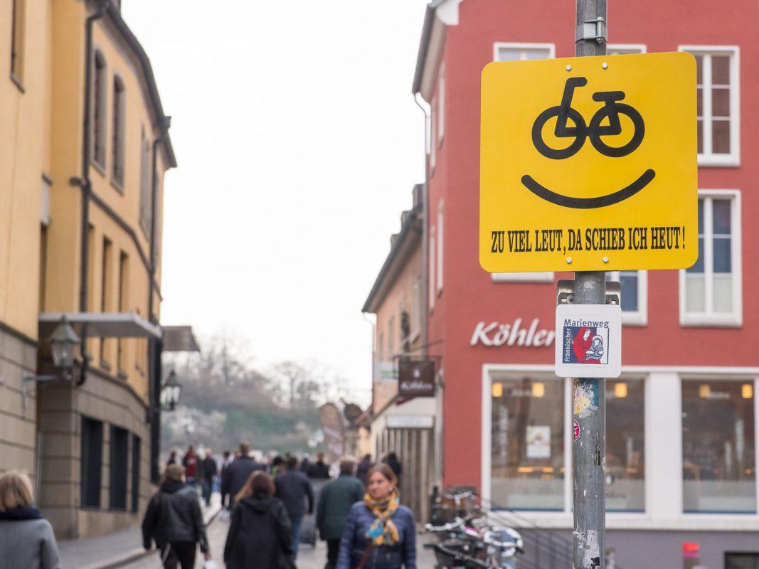 """Das Schild """"Zu viel Leut, da schieb ich heut"""" an der Alten Mainbrücke. Foto: Pascal Höfig"""