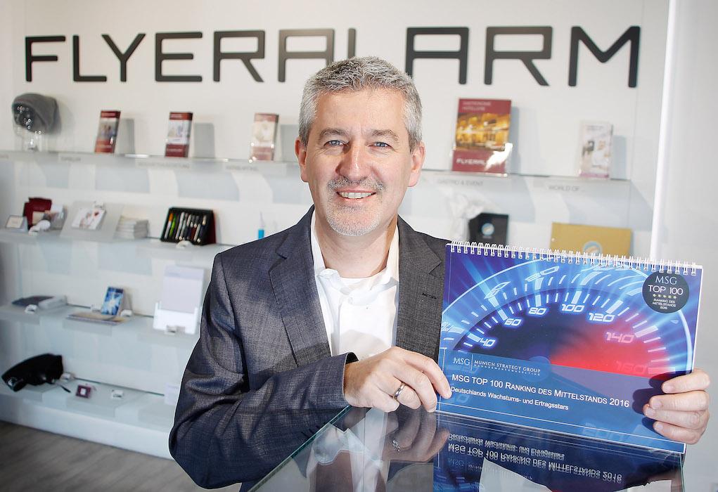 Hartmut Kappes (CFO FLYERALARM Group) zeigt die Studie MSG Top 100. Foto: FLYERALARM