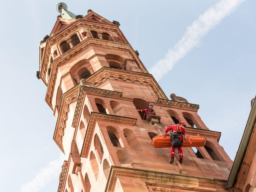 Zentimeter für Zentimeter schweben die beiden Männer nach unten, während ein dritter Mann aus dem Turmfenster heraus die Rettung überwacht. Foto: Pascal Höfig