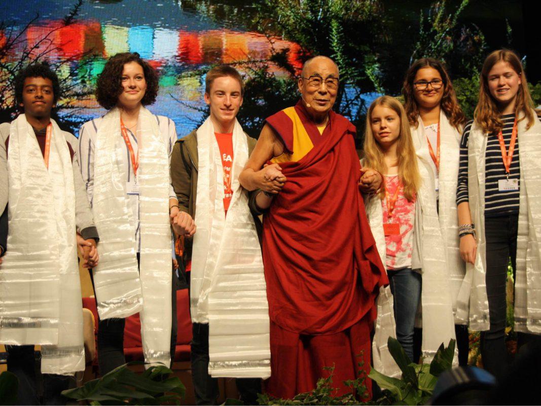 Der Dalai Lama mit zahlreichen Schülern bei seiner Podiumsdiskussion in Frankfurt. Foto: Simone Bernhard-Schwarz