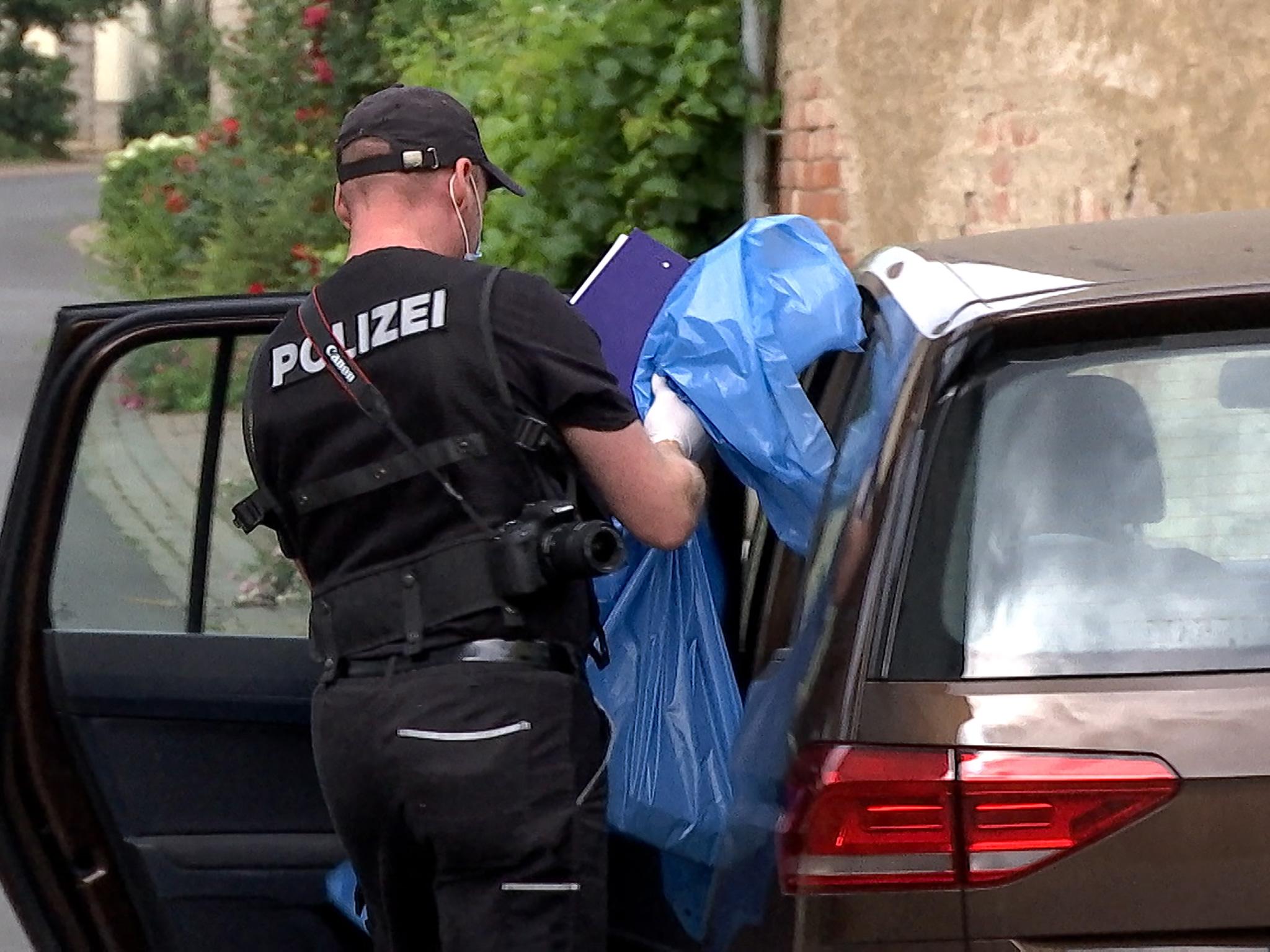 Ein Beamter sichert Beweismitteln aus dem Hof des Beschuldigten. Foto: Sat.1 Bayern