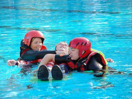 Die angehenden Notfallsanitäter Anne Krönert und David Kraus trainieren im Schwimmbad Rettungstechniken, ihr Kollege Sebastian Sämmer spielt Patient. Foto: Daniel Ostertag / BRK Würzburg