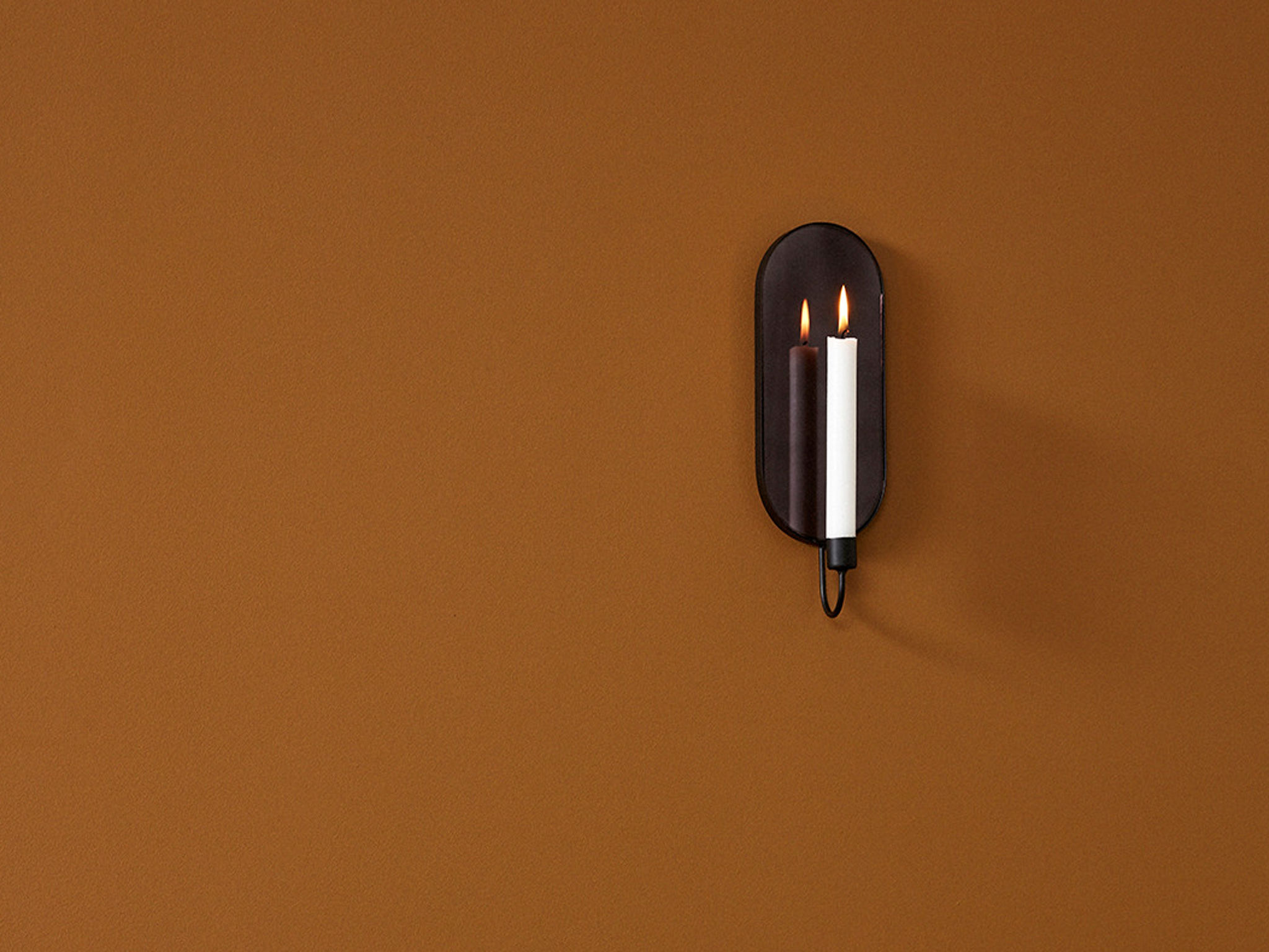 Schlichte Eleganz: Der Spiegel mit Kerzenhalter ist ein Hingucker. Foto: einrichten design
