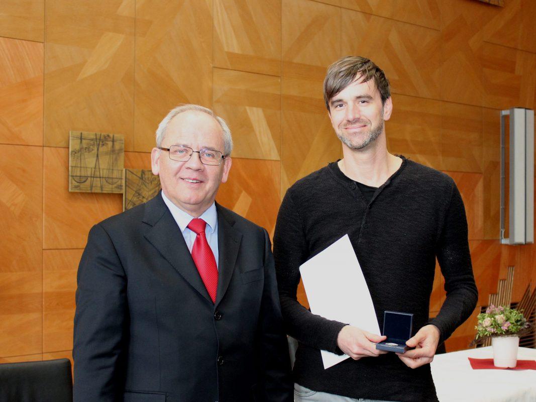 Regierungspräsident Dr. Eugen Ehmann übergibt die Urkunde und Medaille an Gernot Metzler. Foto: Johannes Hardenacke/Regierung von Unterfranken