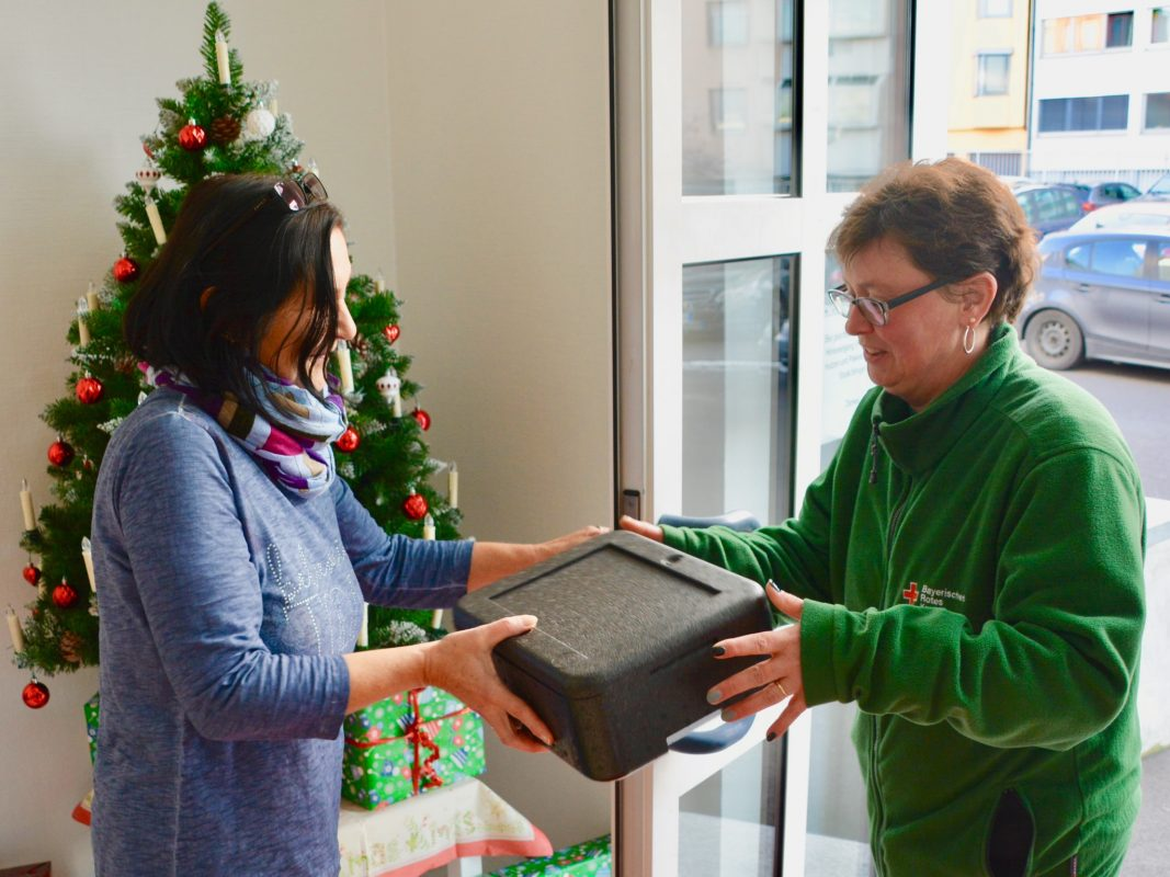 BRK-Mitarbeiterin Claudia Then (rechts) liefert das Weihnachtsmenü warm zu den Kunden nach Hause. Foto: Doku-Team BRK Würzburg