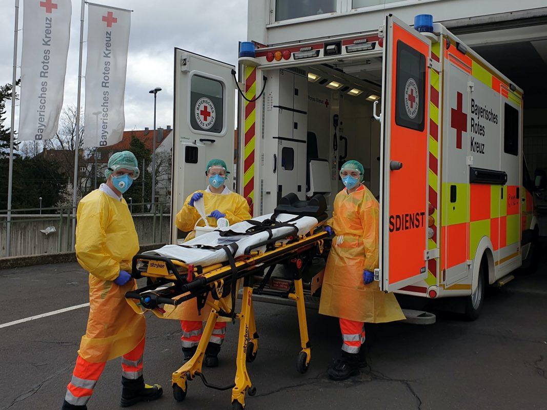 Sanitäter des BRK in Schutzkleidung, wie sie beim Transport von Patienten mit Covid-19-Infektion oder anderen ansteckenden Krankheiten getragen wird. Foto: BRK Würzburg