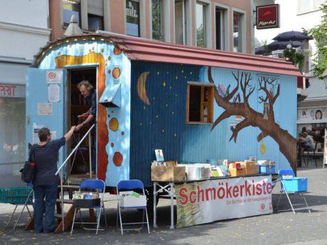 """Im Sommer lädt die """"Schmökerkiste"""" des Fördervereins Wärmestube in der Würzburger Innenstadt zum Lesen und Begegnen ein. Foto: Julia Eyrisch/ Caritas"""