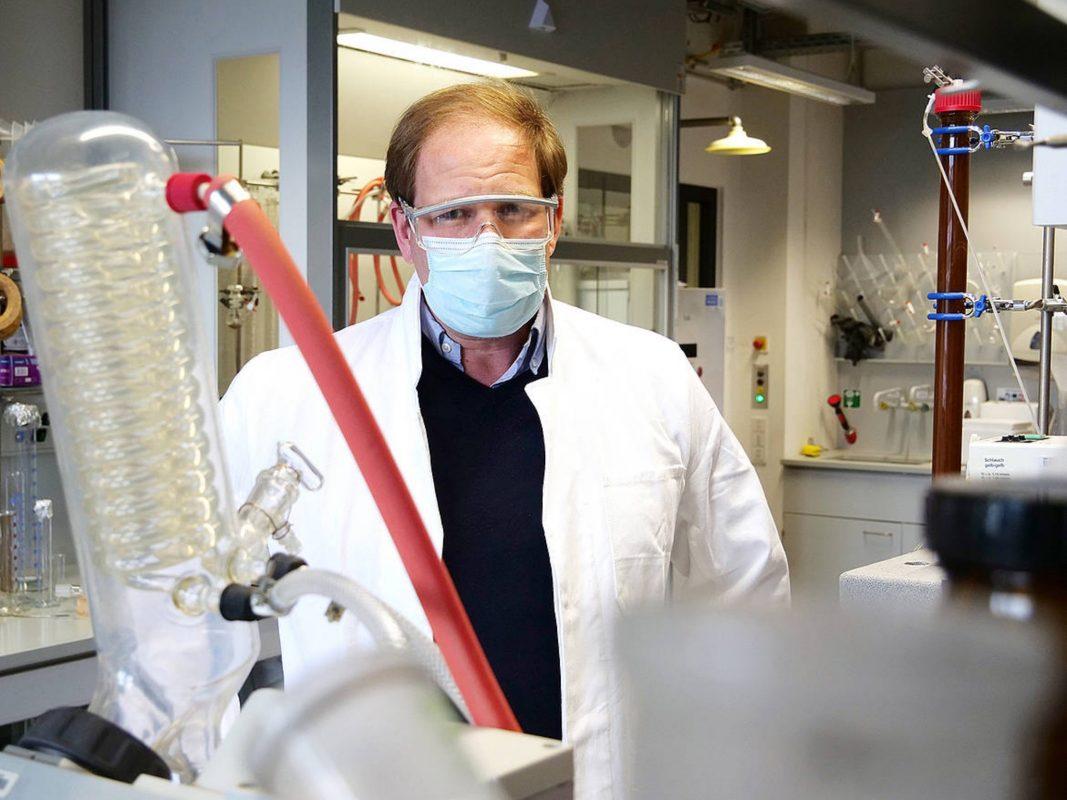 Jürgen Seibel - mit Schutzbrille, wie im Labor vorgeschrieben, und Corona-bedingter Maske. Bild: Gunnar Bartsch / Universität Würzburg