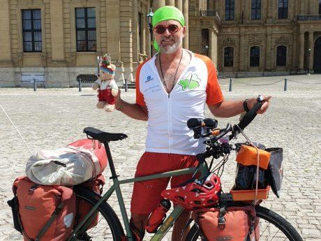 Jörg Richter mit seinem Rad auf dem Würzburger Residenzplatz. Foto: Care-for-Rare Foundation