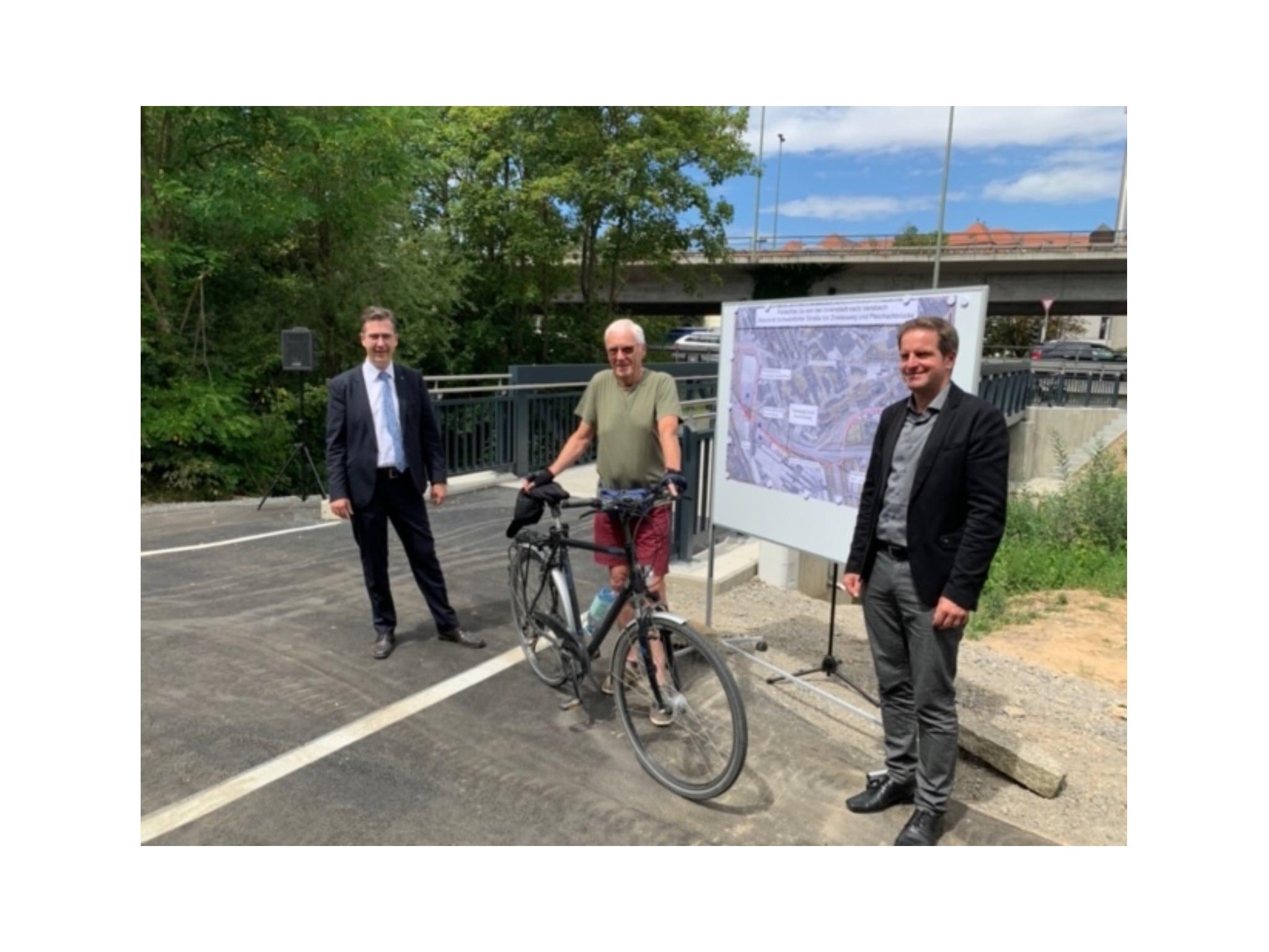 OB Christian Schuchardt und Baureferent Benjamin Schneider begrüßen den ersten Radfahrer auf der neuen Brücke, Bernhard Eiselein aus Rimpar. Foto: Stadt Würzburg