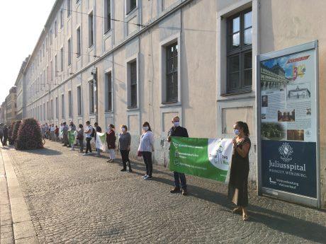 """Am Dienstag bildeten die Demonstrierenden der Kundgebung """"Dienst-Tag für Menschen"""" eine Menschenkette entlang des Juliusspital-Gebäudes. Foto: Jacob Grimm"""