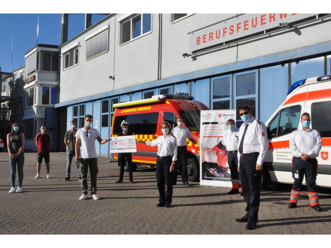 Die gesamte ehrenamtliche Führungsriege der Malteser Würzburg war zur Spendenüber- gabe in die Wache der Berufsfeuerwehr gekommen, um der Wachabteilung 3 und der Fo- tografin Laura Schumacher (links) für die großartige Unterstützung des Malteser Her- zenswunsch-Krankenwagen zu danken. Foto: Christina Gold/Malteser