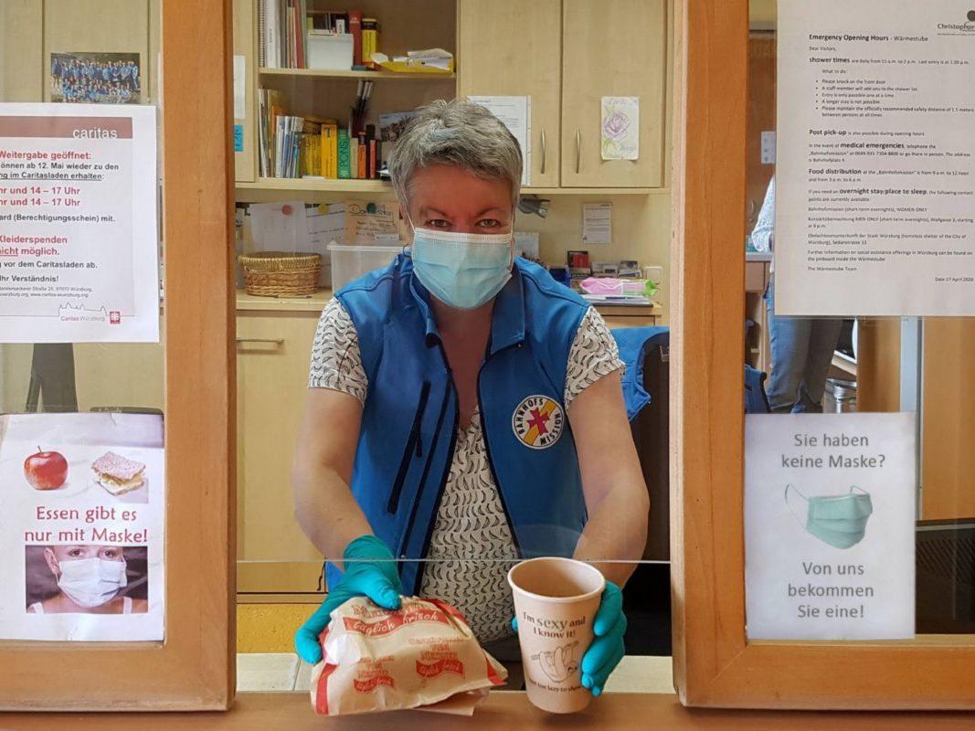 Lilian Stumpf von der Würzburger Bahnhofsmission reicht einem Bedürftigen Lebensmittel. © Foto: Michael Lindner-Jung