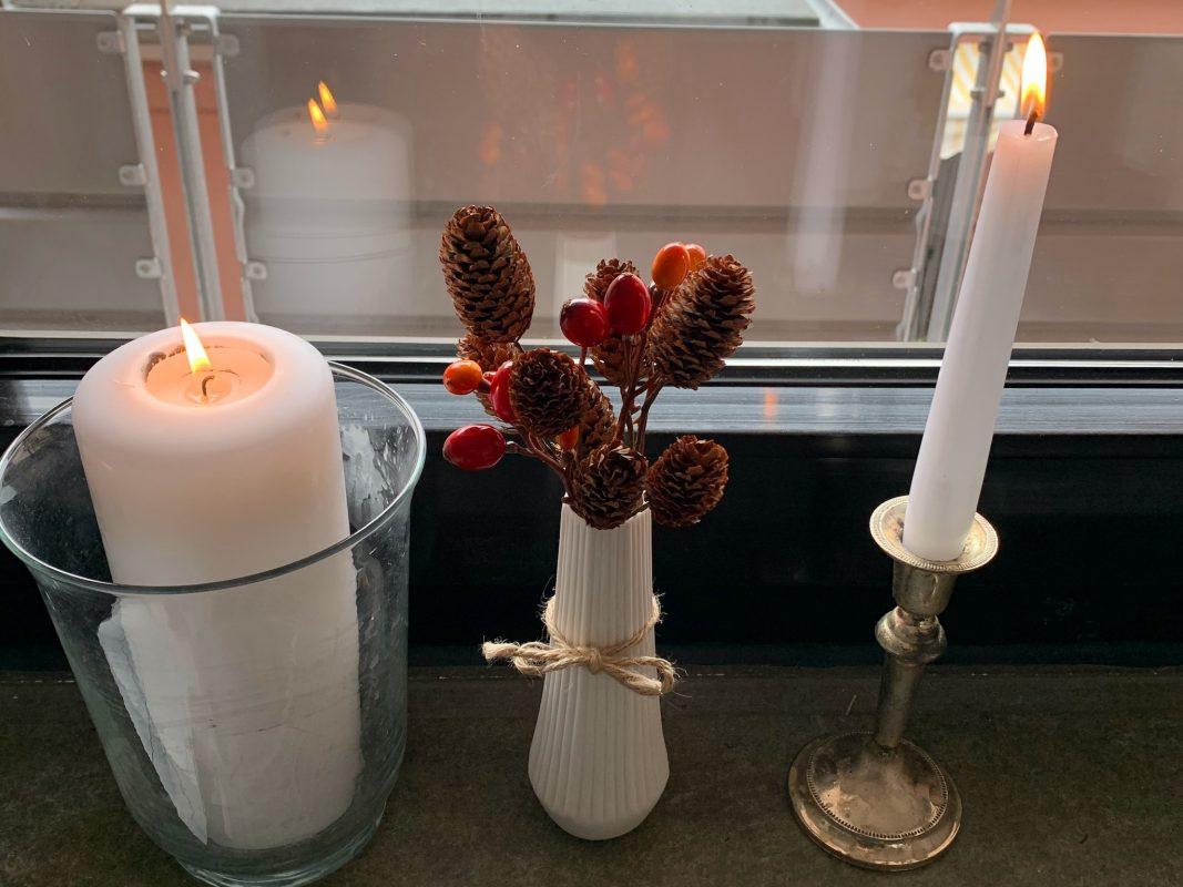 Große Kerzen und eine kleine Vase, gefüllt mit kleinen Tannenzapfen und Hagebutten. Foto: Lilli Müller