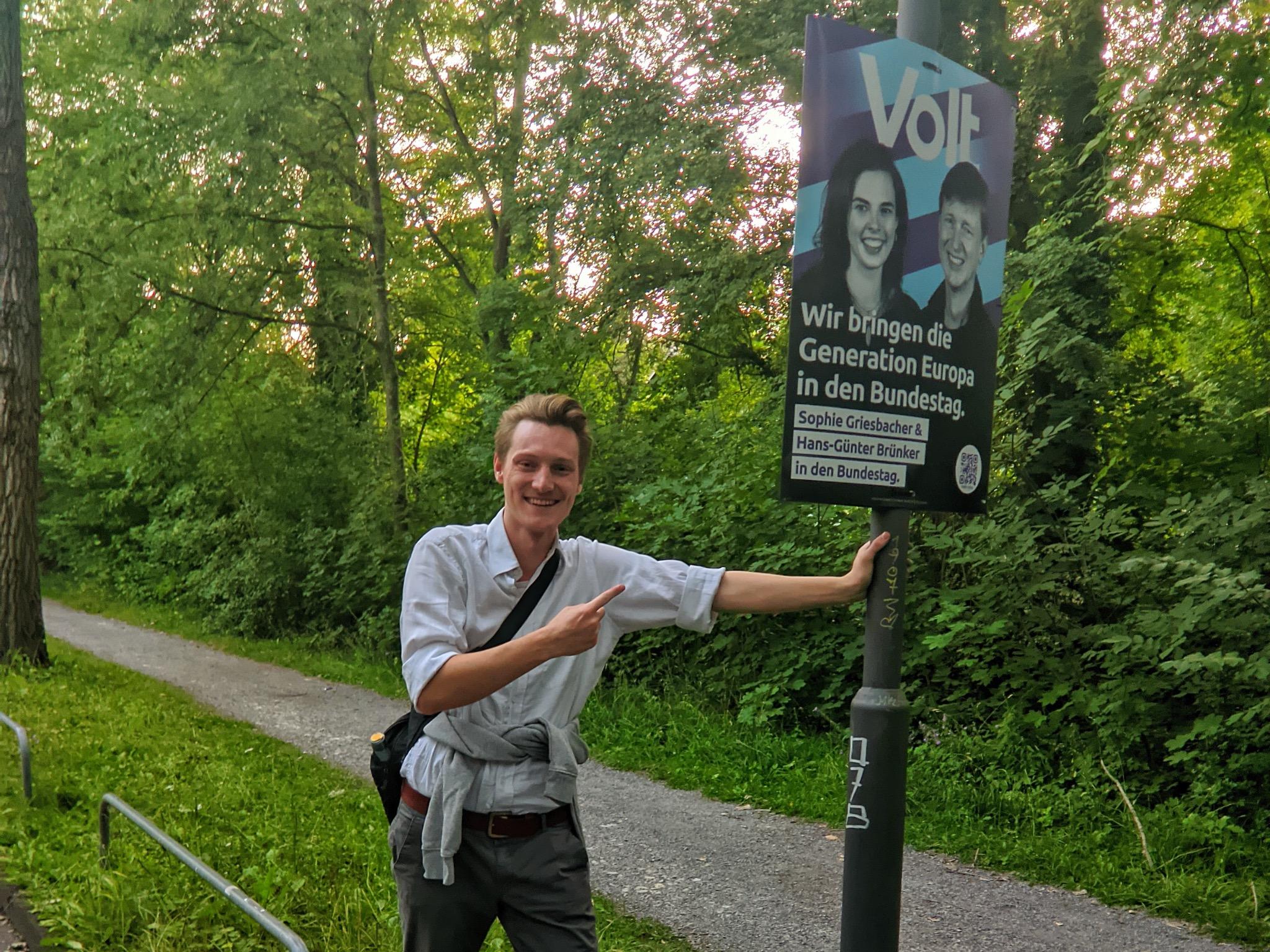 Listenkandidat Kolja Knodel mit einem Wahlplakat am Sebastian-Kneipp-Steg. Foto: Nils Bischof / Volt