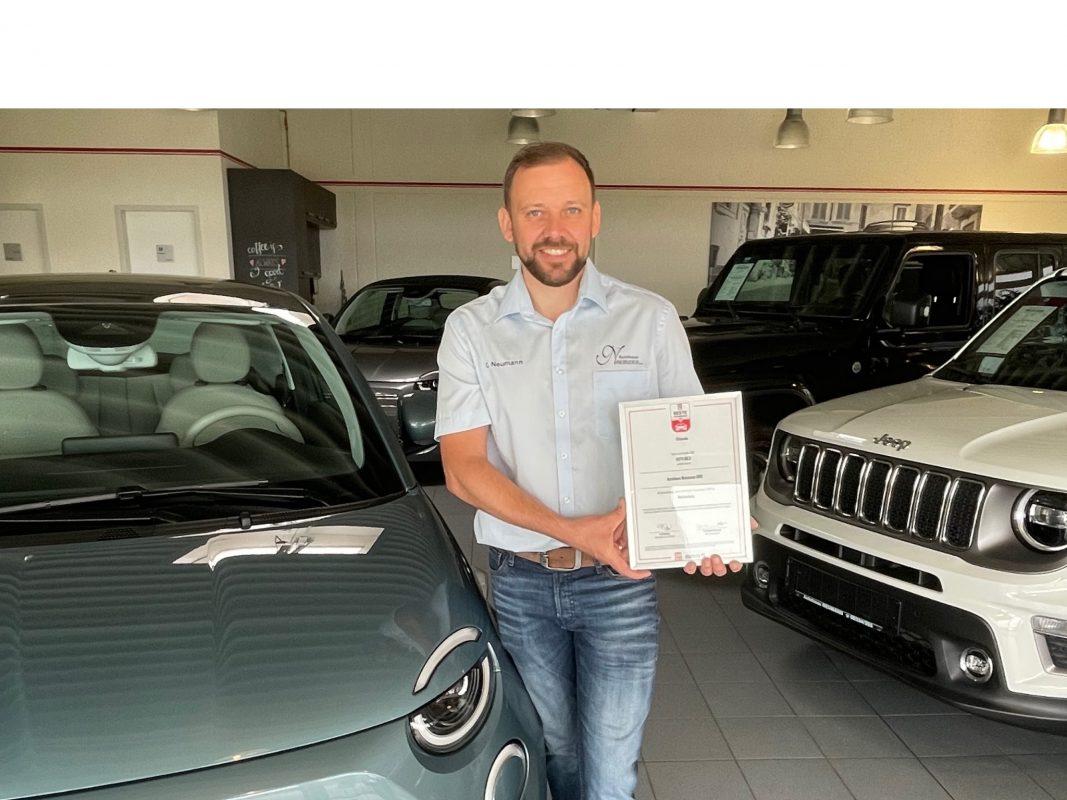 Hat einen Ehrenplatz im Autohaus: Christian Neumann mit der Urkunde. Foto: Autohaus Neumann